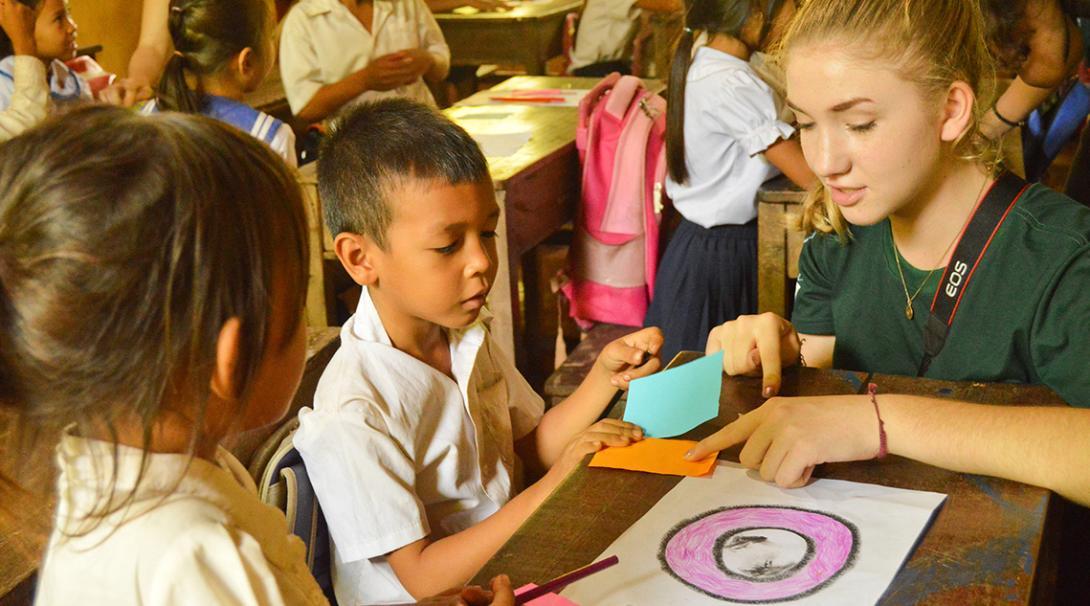 En su voluntariado social en Camboya, una voluntaria organiza actividades en un centro comunitario.